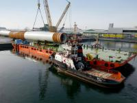 The monopiles are loaded onto the barge in Rostock for the nearshore transport to the Netherlands. (Photo: Otto Wulf GmbH & Co. KG)